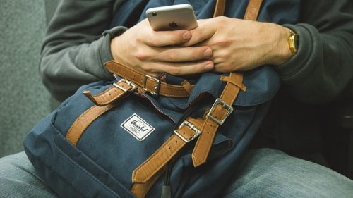 携帯を見るバックパッカー